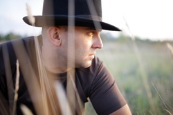 American Cowboy sitting in a field and looks into the distance