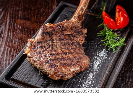 American cuisine. Large juicy grilled steak on a tomahawk bone. Beef steak on a wooden board with rosemary and salt. background image, copy space text