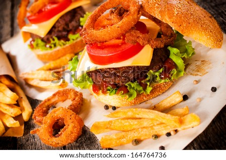American cuisine with cheeseburger, onion rings and french fries.Selective focus on the cheeseburger
