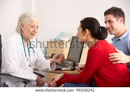 American doctor talking to happy couple in surgery