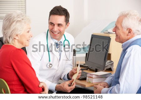 American doctor talking to senior couple in surgery