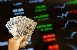 American dollar and Turkish lira on woman's hand and stock market screen, money chart background
