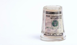 American dollar bills in an inverted glass on a white background