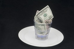 American dollar bills on plate with glass on black background
