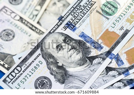 American dollars. A stack of hundred dollar bills. Close up of new hundred dollar bill on the blue background.