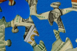 American dollars of different denominations are hidden under the puzzle pieces. Blue puzzles. Top view, Flat lay.