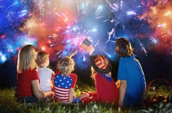 American family celebrating Independence Day. Picnic and fireworks on 4th of July in America. USA flag. Parents and kids celebrate US holiday. Children watching firework.