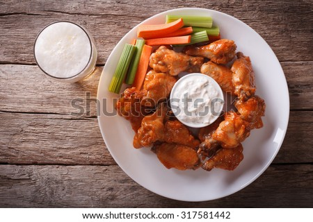 American fast food: buffalo wings with sauce and beer on the table. horizontal view from above #317581442