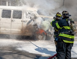 American firefighters use a hose and firefighting foam to extinguish a van fire