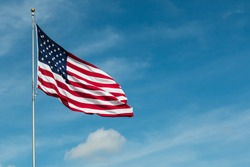 American Flag against the backdrop of a blue sky and clouds.