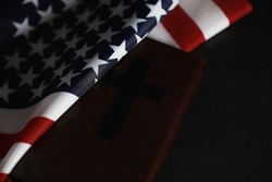 American flag and holy bible book on mirror background. Symbol of the United States and religion. Bible and striped flag on a black background.
