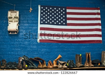 American flag and used boots in thrift store - stock photo
