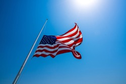 American flag at half mast waving in strong wind after memorial service , bright sunshine and blue sky on a nice Texas clear day looking up at perfect flagpole and perfect American flag
