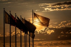 American flag baclkit by sun at cloudy sunset waving in wind left to right with a group of other flags sihouetted