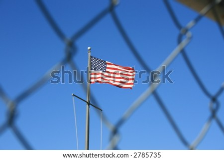 American flag behind a chain link fence.