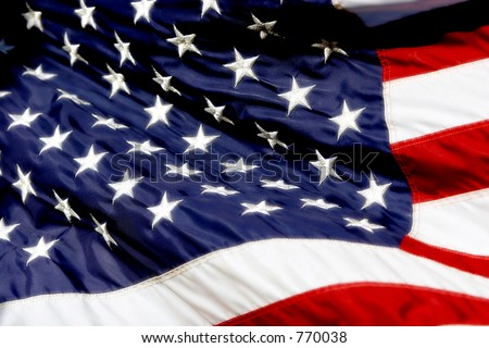 American Flag billowing in the wind, with high color and radiant whites.