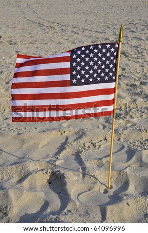 American flag blows in wind on sandy beach, perfect for cover art