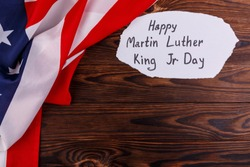 American flag close-up in the upper left corner with an inscription on a wooden background