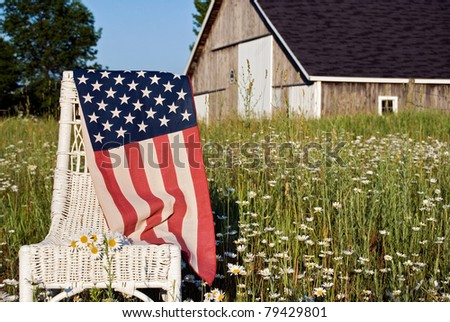 american flag draped over wicker chair in daisy field