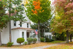 American flag flies outside  in street of residential American style homes in wooded suburb in fall with colors and leaf fall starting.