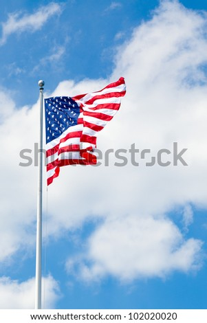 American flag flying against blue sky with white clouds.  Room for text