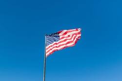 American flag flying in a city