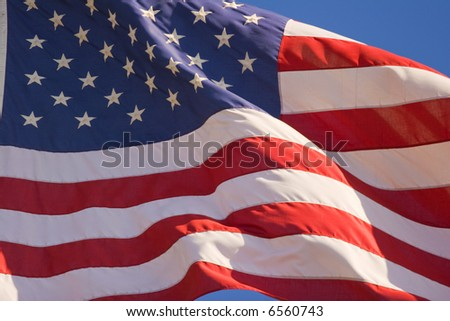 American flag flying in the wind on flag pole against blue sky