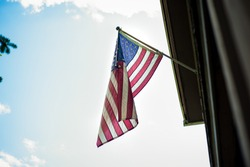 American Flag Flying on Pole on House Porch Blue Sky Memorial Day