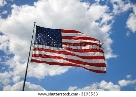 American flag flying with blue sky and white cloud background - stock photo