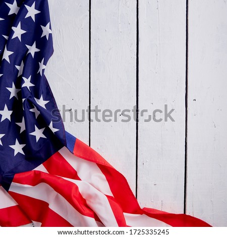 American Flag for the America's 4th of July Celebration over a white wooden rustic background to mark America's Independence Day. Image shot from top view.