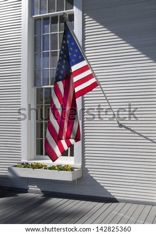 American flag hanging in front of a colonial window frame