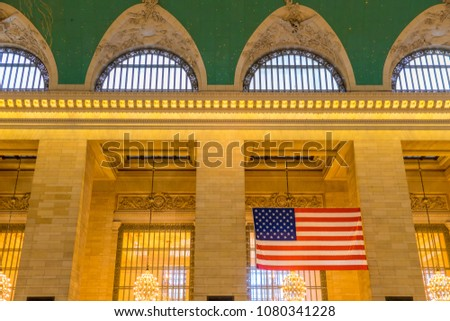 American Flag hanging in the main hall at Grand Central Terminal. This historic train terminal is a world-famous landmark in Midtown Manhattan. #1080341228