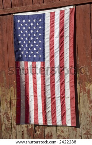 American flag hanging verticle on an old red new england barn