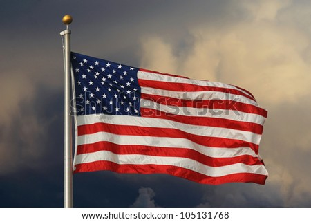 American flag in foreground, waving and brightly lit with ominous clouds in the background. / Old Glory Aglow / Brightly lit stars and stripes.