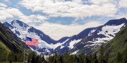 American flag in the foreground with snow-capped mountains in the background in Alaska in July.