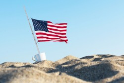 American flag in the sand against a blue  sky in the cup of coffee. Concept