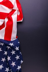 American flag lies vertically on the left close-up on a gray background
