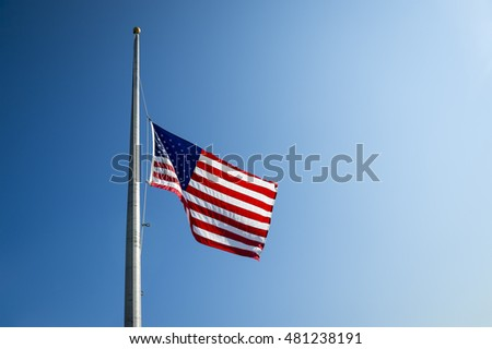 American flag lowered to half mast in bright blue sky