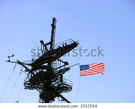 American flag on a US navy war ship mast tower flying in the wind over blue sky