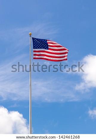 American Flag on Flagpole Waving in Blue Sky