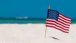 American Flag on the Beach. 4th of July Independence, Memorial or Presidents Day. US starry striped patriotic symbol. United States Holidays. Summer vacations. Ocean sand. Bright sunny day. Salt water