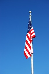 American flag on the pole against blue sky, no wind or waving