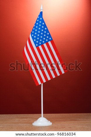 American flag on the stand on wooden table on red background