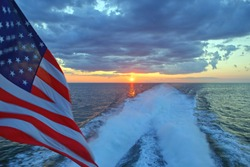 American flag over a boat wake at sunset.