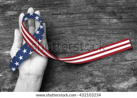 Shutterstock American flag pattern awareness ribbon color splashed on human hand grunge background: United states of america public holiday USA national day, nationalism raising US nation support campaign concept