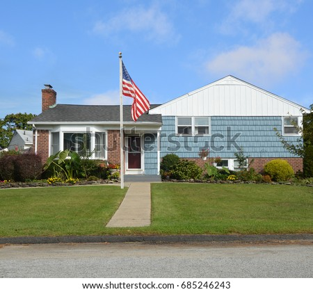 American flag pole front yard lawn of Suburban home ranch style house bay window USA blue sky clouds #685246243