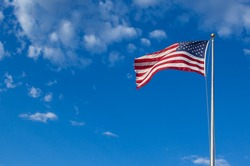 American flag - star and stripes floating over a cloudy blue sky