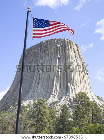American flag waving in a breeze over Devils Tower