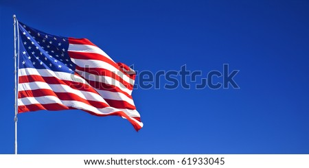 American flag waving in blue sky