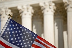 American flag waving in front of the U.S. Supreme Court building columns on Capitol Hill in Washington, DC